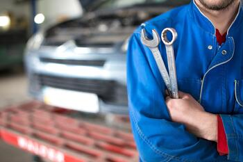 Auto shop technician holding tools in a service garage ready to address customer dispute