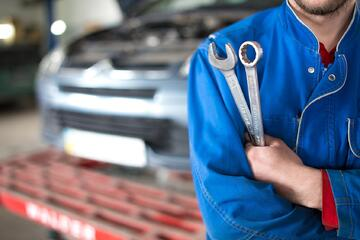 Auto shop worker holding tools and preparing to perform service repairs on a vehicle