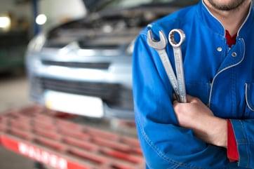 Technician posing in an auto shop during the busy season