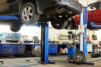 Vehicles on lifts in a transmission rebuild shop