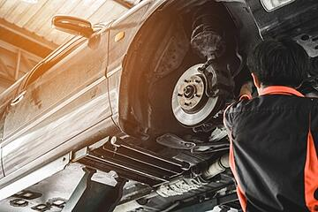 Auto shop technician inspecting a vehicle on a lift in the garage