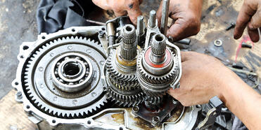Technician rebuilding a disassembled transmission unit on a workbench