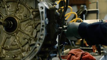 Transmission technician rebuilding a unit on a workbench